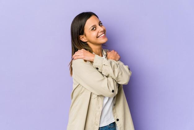 Giovane donna isolata su sfondo viola abbracci, sorridente spensierata e felice.