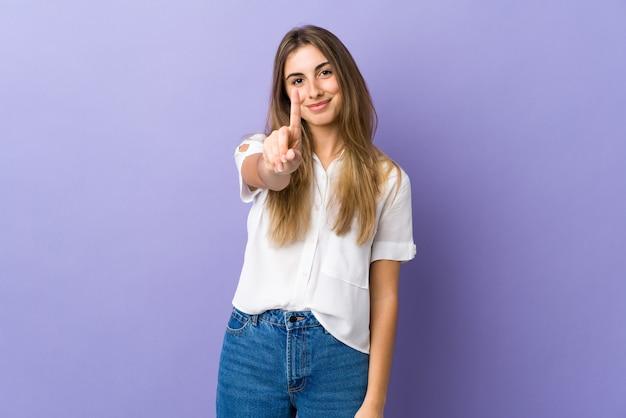 Giovane donna sulla rappresentazione viola isolata e alzando un dito
