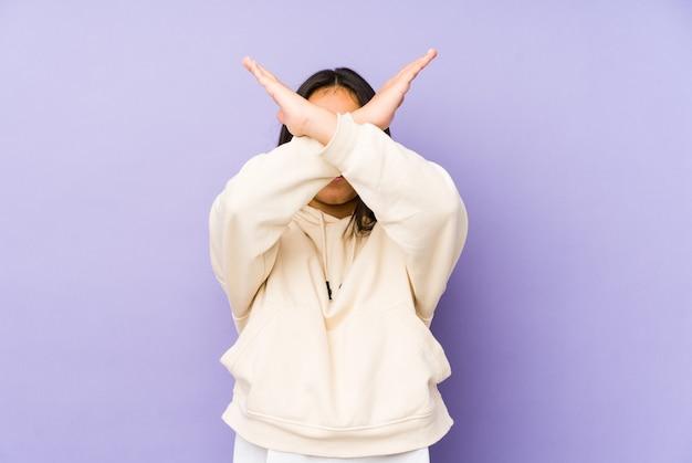Giovane donna isolata su uno spazio viola mantenendo due braccia incrociate, concetto di negazione.