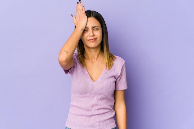 Giovane donna isolata sul muro viola dimenticando qualcosa, schiaffeggiando la fronte con il palmo e chiudendo gli occhi.
