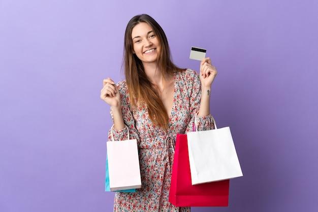 Giovane donna isolata sulla parete viola che tiene i sacchetti della spesa e una carta di credito