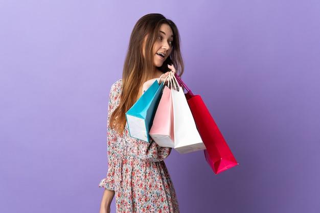 Giovane donna isolata sulla parete viola che tiene le borse della spesa e guardando indietro