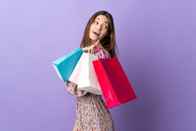 Giovane donna isolata sulla parete viola che tiene i sacchetti della spesa e sorridente