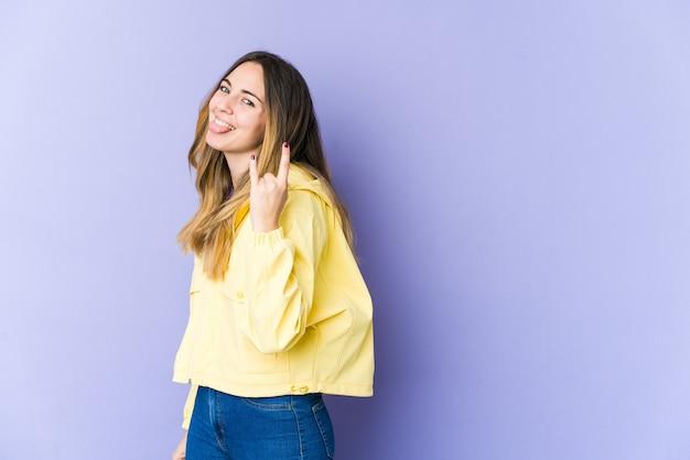Giovane donna isolata sulla parete viola che mostra gesto di roccia con le dita