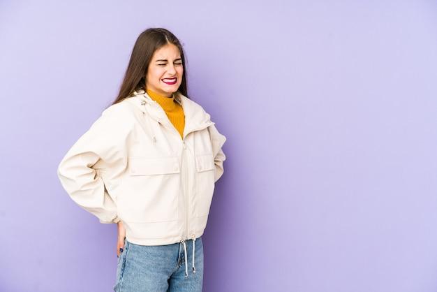 Giovane donna isolata sulla parete viola che soffre di mal di schiena