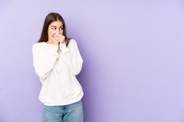 Giovane donna isolata sulla parete viola premurosa alla ricerca di uno spazio di copia che copre la bocca con la mano