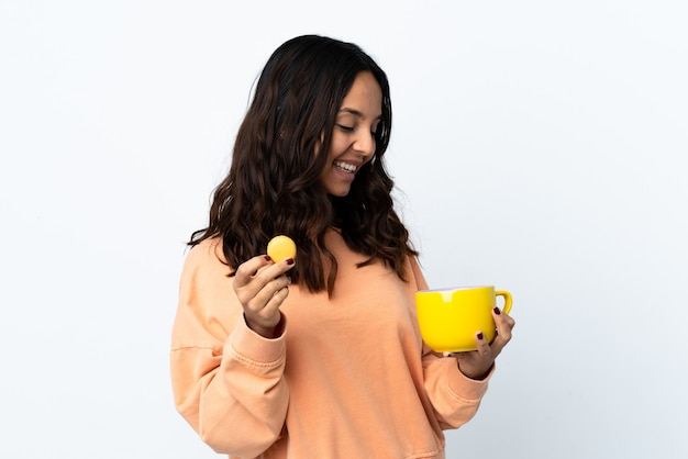 Giovane donna su sfondo bianco isolato tenendo colorati macarons francesi e una tazza di latte