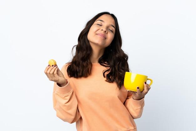 Giovane donna sopra bianco isolato che tiene macarons francesi colorati e una tazza di latte