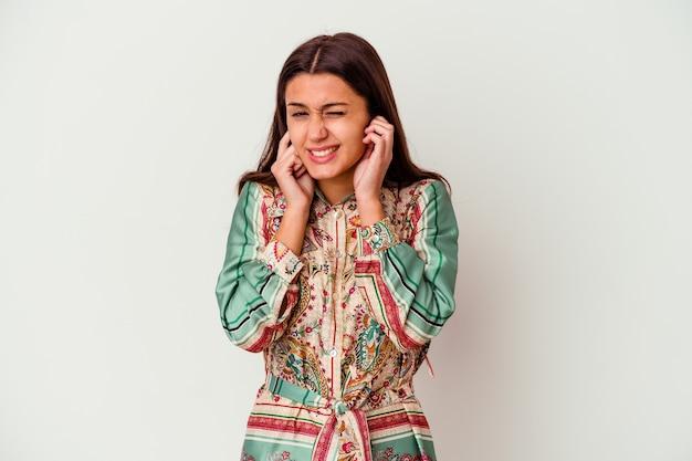 Giovane donna isolata sul muro bianco che copre le orecchie con le mani