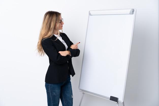 Giovane donna sopra la parete bianca isolata che dà una presentazione sul bordo bianco e che lo indica