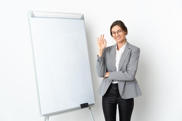 Giovane donna isolata sulla parete bianca che dà una presentazione sulla lavagna bianca e che mostra segno giusto con le dita