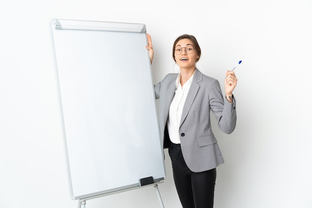 Giovane donna isolata sulla parete bianca che dà una presentazione sulla lavagna bianca