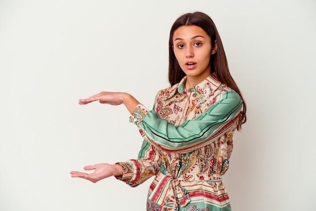 Giovane donna isolata sulla parete bianca scioccata e stupita tenendo uno spazio di copia tra le mani