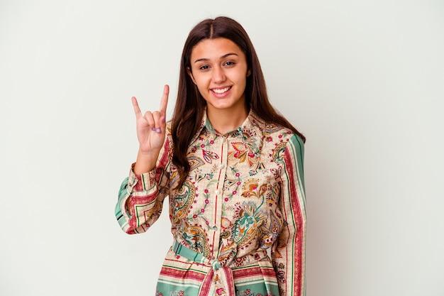 Giovane donna isolata sul muro bianco che mostra un gesto di corna come un concetto di rivoluzione