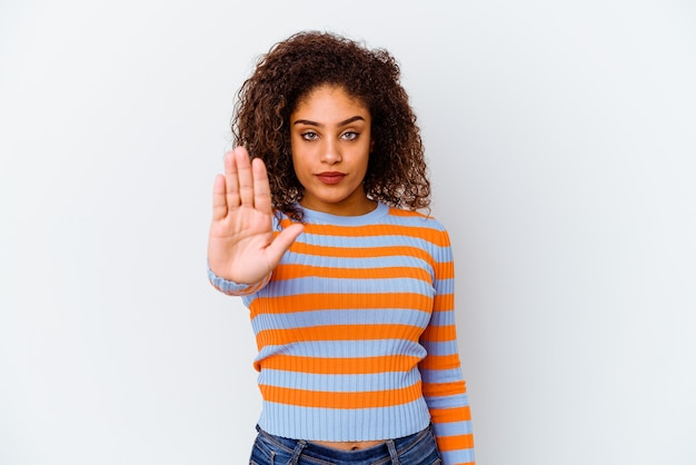 Giovane donna isolata sul muro bianco in piedi con la mano tesa che mostra il segnale di stop, impedendoti