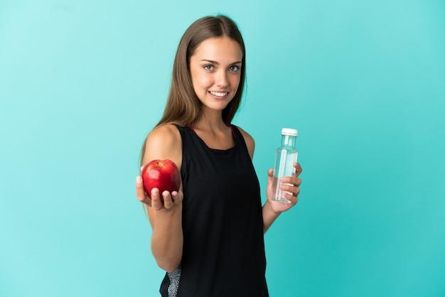 Giovane donna isolata con una mela e con una bottiglia d'acqua