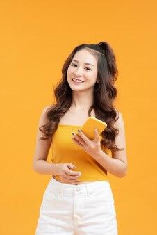Giovane donna su sfondo giallo isolato che invia un messaggio con il cellulare