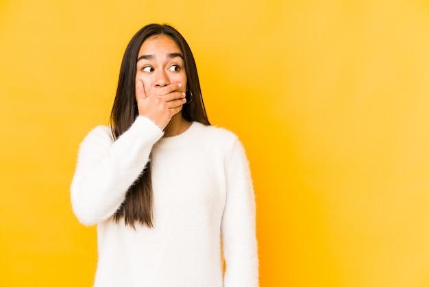 Giovane donna isolata su uno sfondo giallo riflessivo alla ricerca di uno spazio di copia che copre la bocca con la mano.