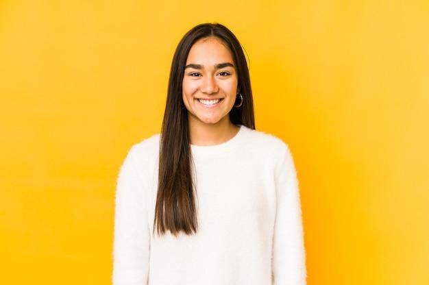 Giovane donna isolata su un giallo felice, sorridente e allegro.