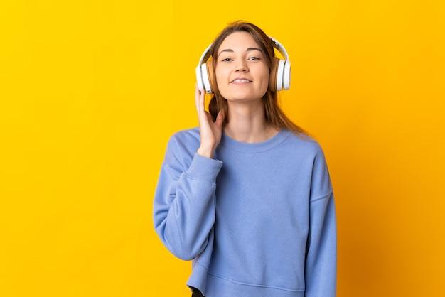 Giovane donna isolata sulla musica d'ascolto della parete gialla
