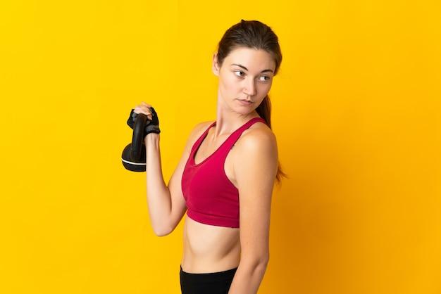 Giovane donna isolata sulla parete gialla che fa sollevamento pesi con kettlebell