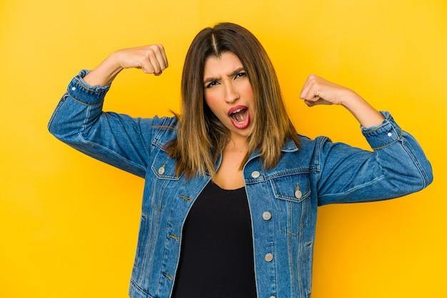 Giovane donna isolata sulla parete gialla che mostra il gesto di forza con le braccia