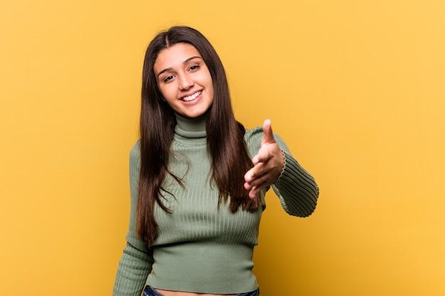 Giovane donna isolata sulla parete gialla che allunga la mano nel gesto di saluto.