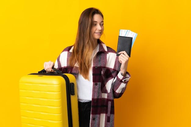 Giovane donna isolata sulla parete gialla in vacanza con la valigia e il passaporto