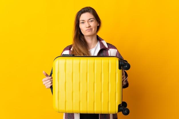 Giovane donna isolata sulla parete gialla in vacanza con la valigia di viaggio