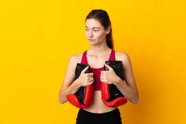 Giovane donna isolata sulla parete gialla con i guantoni da boxe