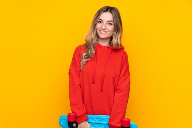 Giovane donna sopra la parete gialla isolata con un pattino con espressione felice