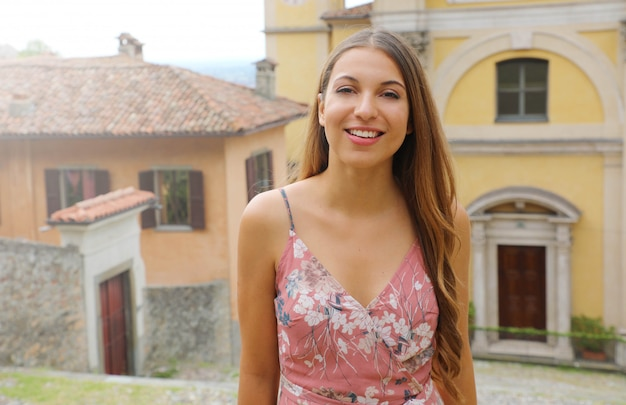 La giovane donna nella vecchia città italiana esamina la macchina fotografica.