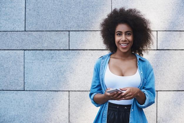 Giovane donna in giacca di jeans stile libero sulla strada isolata su