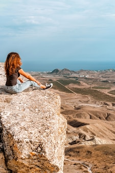 Una giovane donna in jeans si siede su una roccia nella valle in crimea