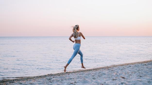 Giovane donna che pareggia in riva al mare