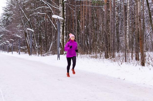 Giovane donna che fa jogging su un parco innevato in una giornata invernale