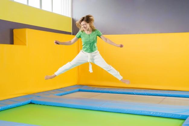 La giovane donna che salta e che rimbalza su un trampolino nel centro sportivo