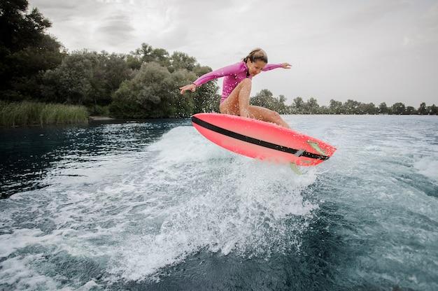 La giovane donna che salta sull'onda tagliente blu contro il cielo grigio