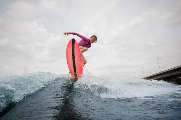 La giovane donna che salta sull'onda blu contro il cielo grigio