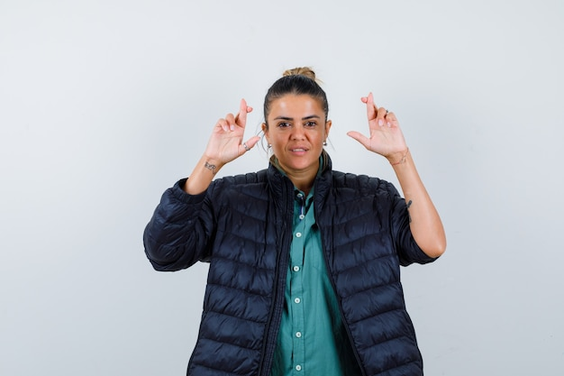 Giovane donna che tiene le dita incrociate in camicia, piumino e sembra fortunata, vista frontale.