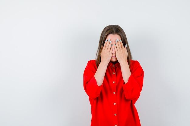 Giovane donna che tiene le mani sul viso in camicetta rossa e sembra depressa. vista frontale.