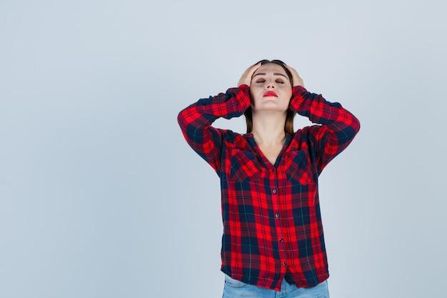 Giovane donna che tiene le mani sulla testa in camicia a quadri e sembra affaticata. vista frontale.
