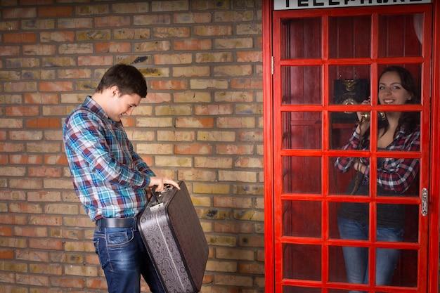 Giovane donna che fa aspettare il marito mentre sta chiacchierando in una cabina telefonica pubblica mentre lui sta fuori con una valigia che controlla l'orologio