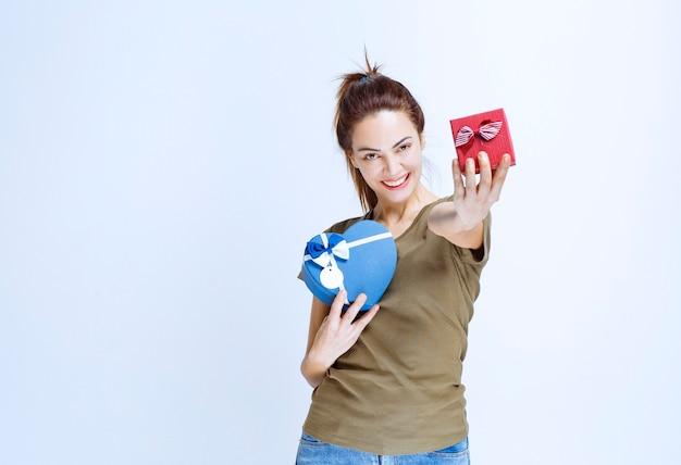 Giovane donna che tiene una delle sue due scatole regalo e restituisce la seconda