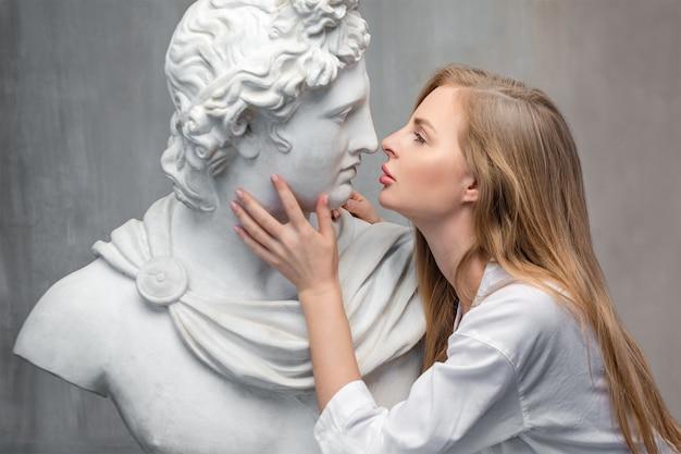 Giovane donna che bacia la scultura del busto di dio apollo.