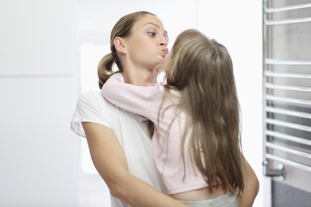 Giovane donna che bacia bambina in bagno