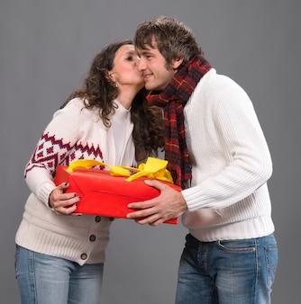 Giovane donna che bacia un uomo con una casella presente su un muro grigio