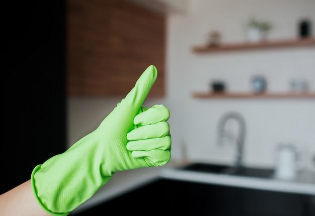 Giovane donna in cucina durante la quarantena. la mano femminile in guanto verde tiene il grande pollice in su. interiore della cucina con sfondo sfocato.