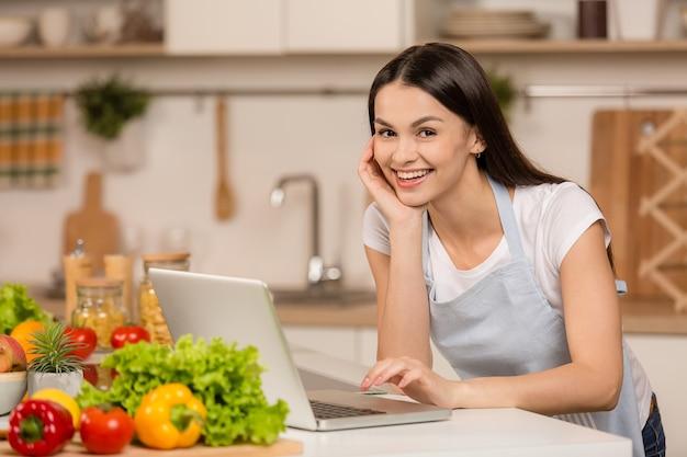 Giovane donna in cucina con computer portatile cercando ricette, sorridendo. concetto di blogger alimentare