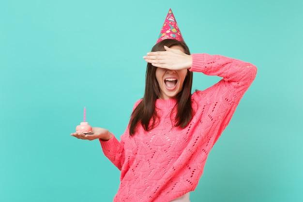 Giovane donna in maglione rosa lavorato a maglia, cappello di compleanno che tiene la bocca spalancata, copre gli occhi con la mano, tiene la torta con una candela isolata su sfondo blu. concetto di stile di vita della gente. mock up copia spazio.